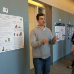 A graduate student presenting a poster to attendees at the 2016 UConn Language Fest.