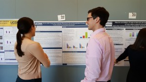 """Attendees discuss the poster """"SLI in ASD: Exploring Language phenotypes beyond standardized testing"""" at the 2016 UConn Language Fest."""