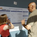"A student presents to an attendee on their poster ""Neural processing on non-speech sounds in bilinguals"" at the 2016 UConn Language Fest."