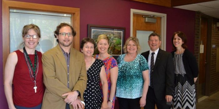 SLHS faculty stand in the UConn Speech and Hearing Clinic lobby. From left to right, Dr. Jennifer Tufts; Dr. Adrian Garcia-Sierra; Dr. Jill Raney; Dr. Erika Skoe; Dr. Lendra Friesen; Dr. Bernard Grela; Dr. Kathleen Cienkowski