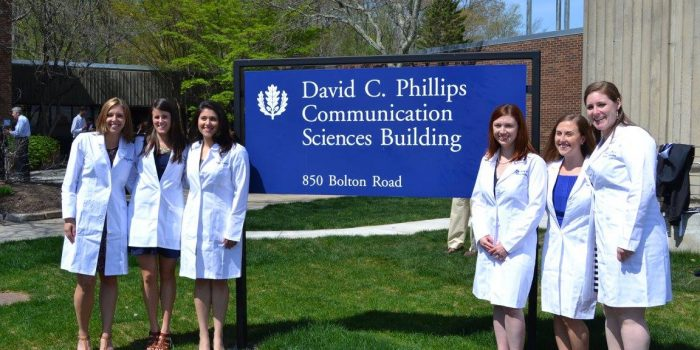 Newly minted Doctors of Audiology pose in front of the David C. Phillips Communication Sciences Building sign in their white coats.