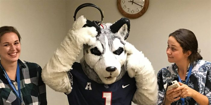 Two SLP graduate students jokingly perform a hearing test on the UConn mascot Jonathan, who do to his ears, is unable to put on the headphones.
